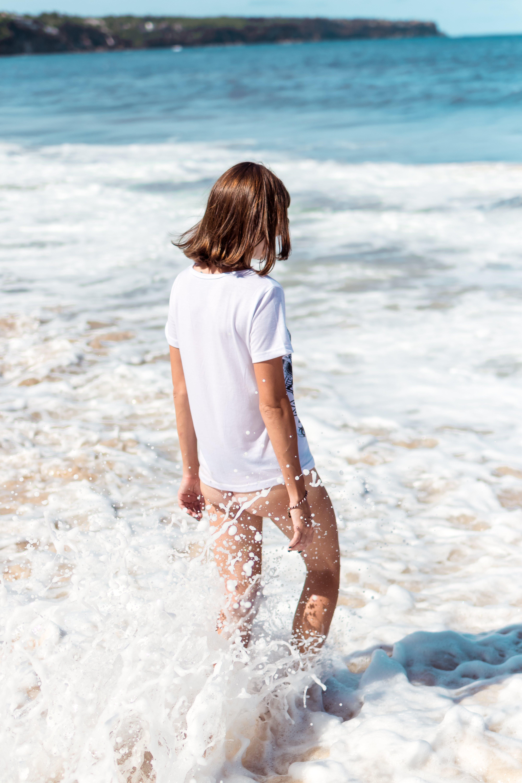 Woman in White Top Walking on Beach Side