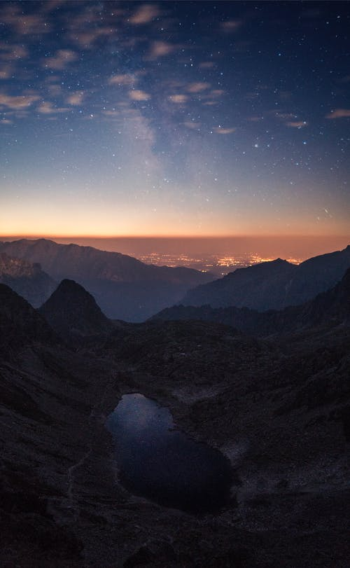 Crater Between Mountains Under Blue Sky White Clouds and Stars during Sunset