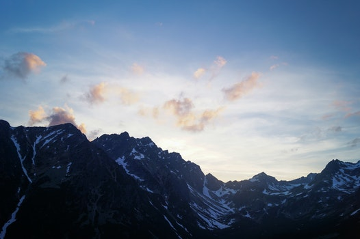 Black Mountain With White Snow Under Blue Sky