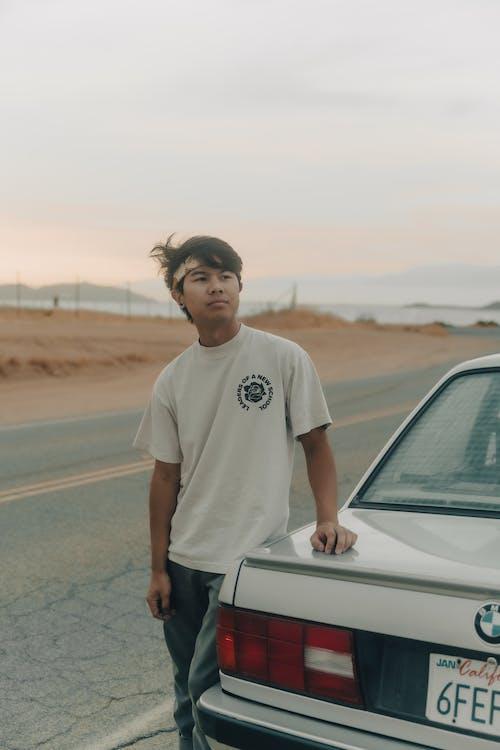 Man in White Crew Neck T-shirt Standing Beside White Car