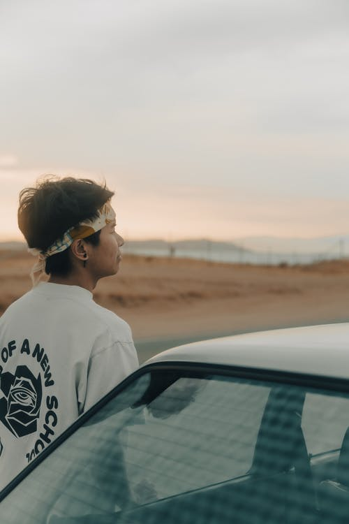 Woman in White Crew Neck T-shirt Standing Beside Car