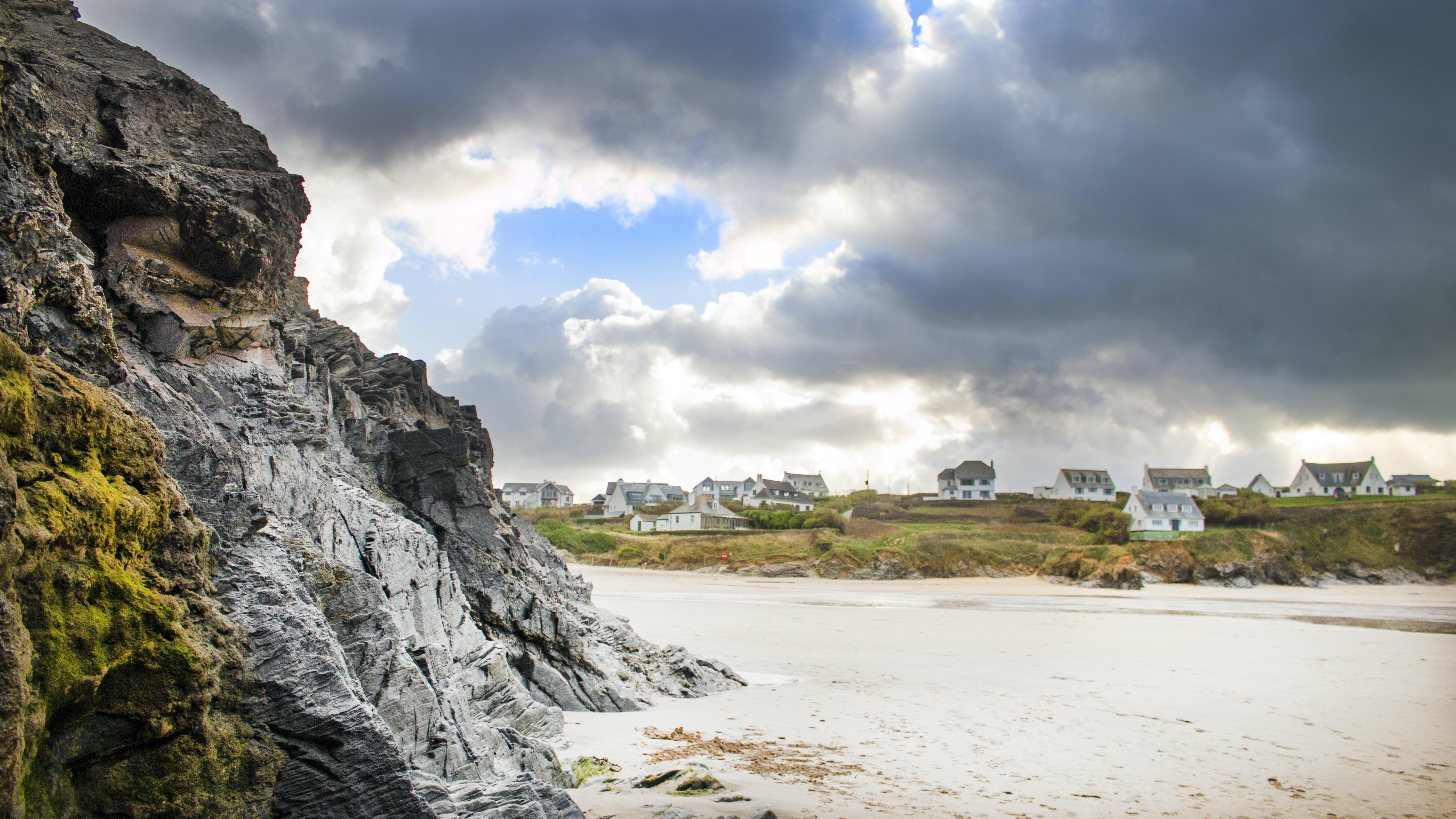 White Sand Beside Grey Rock Cliff
