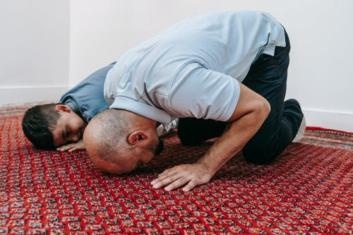Father ang Son Kneeling on the Ground