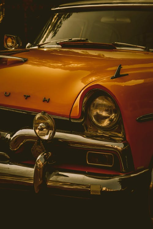 Polished retro car with shiny chrome details parked on street