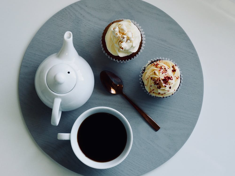 White Ceramic Cup and Teapot with Cupcakes