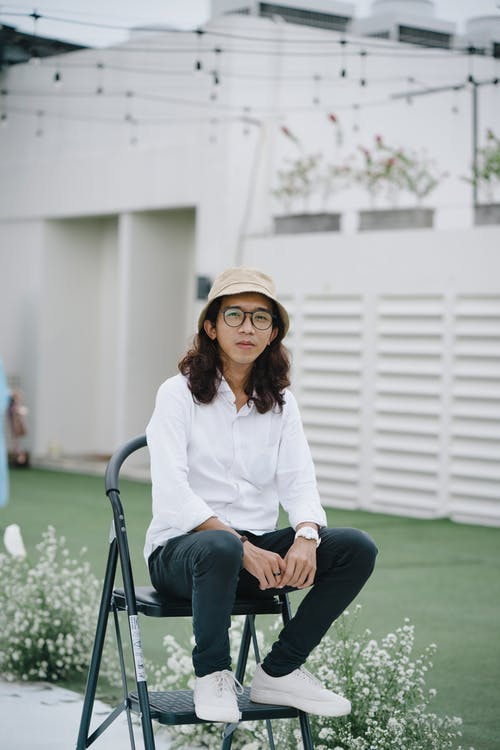 Woman in White Long Sleeve Shirt Sitting on Black Metal Chair