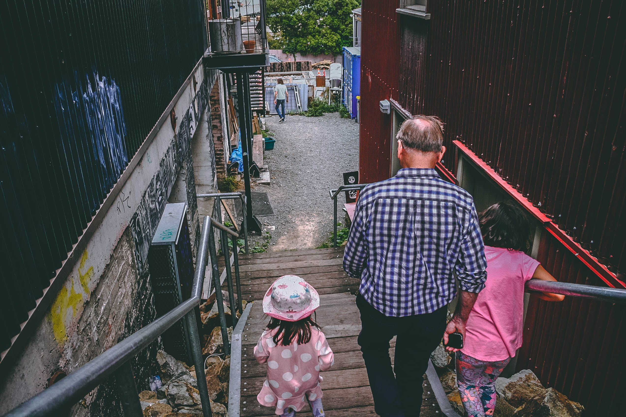 Man and Two Girls Walking Down on Stairs