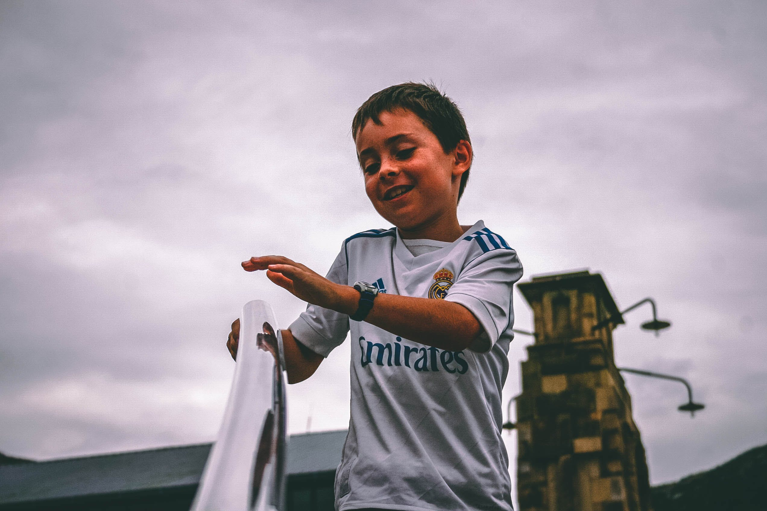 Boy in White and Blue Fly Emirates Jersey Shirt Holding on Stairs Grab Bar Under Gray Skies