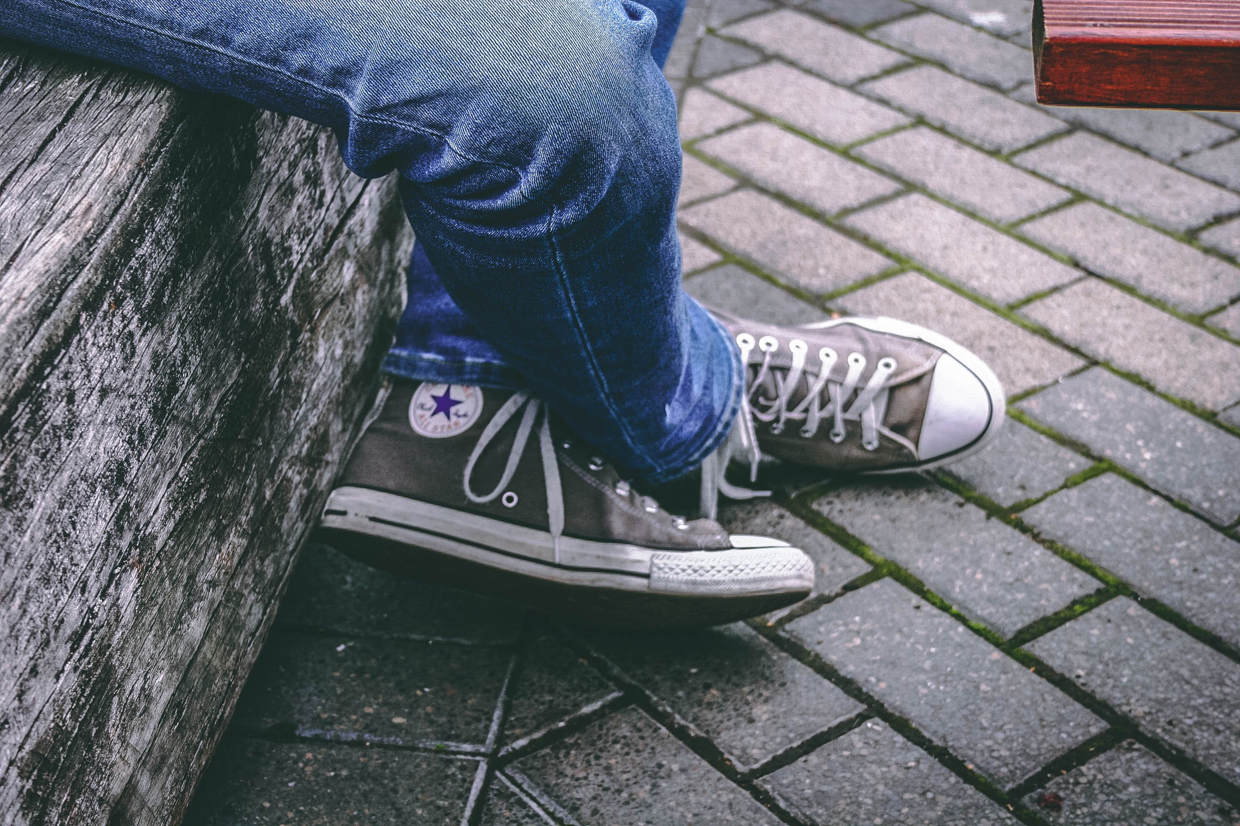Person Wearing Brown Converse All-star High-top Sneakers and Blue Denim Jeans While Sitting on Bench