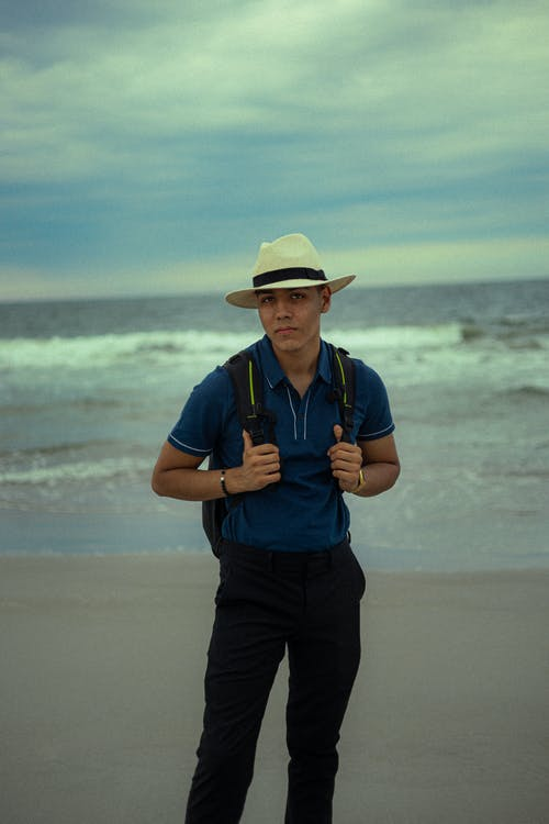 Man in Blue Polo Shirt and Black Pants Wearing Brown Hat Standing on Beach