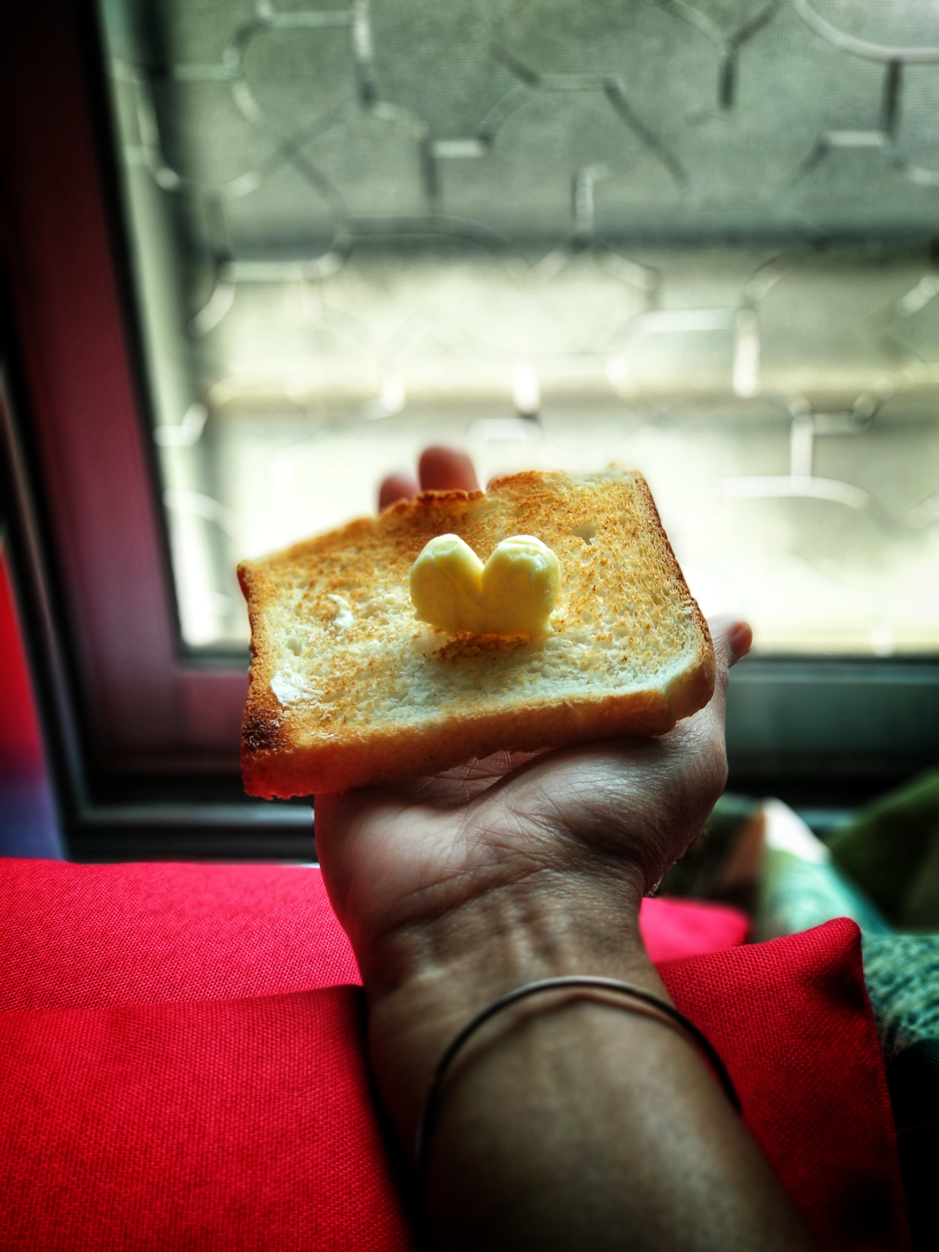 Person Holding Toast With Butter on Top