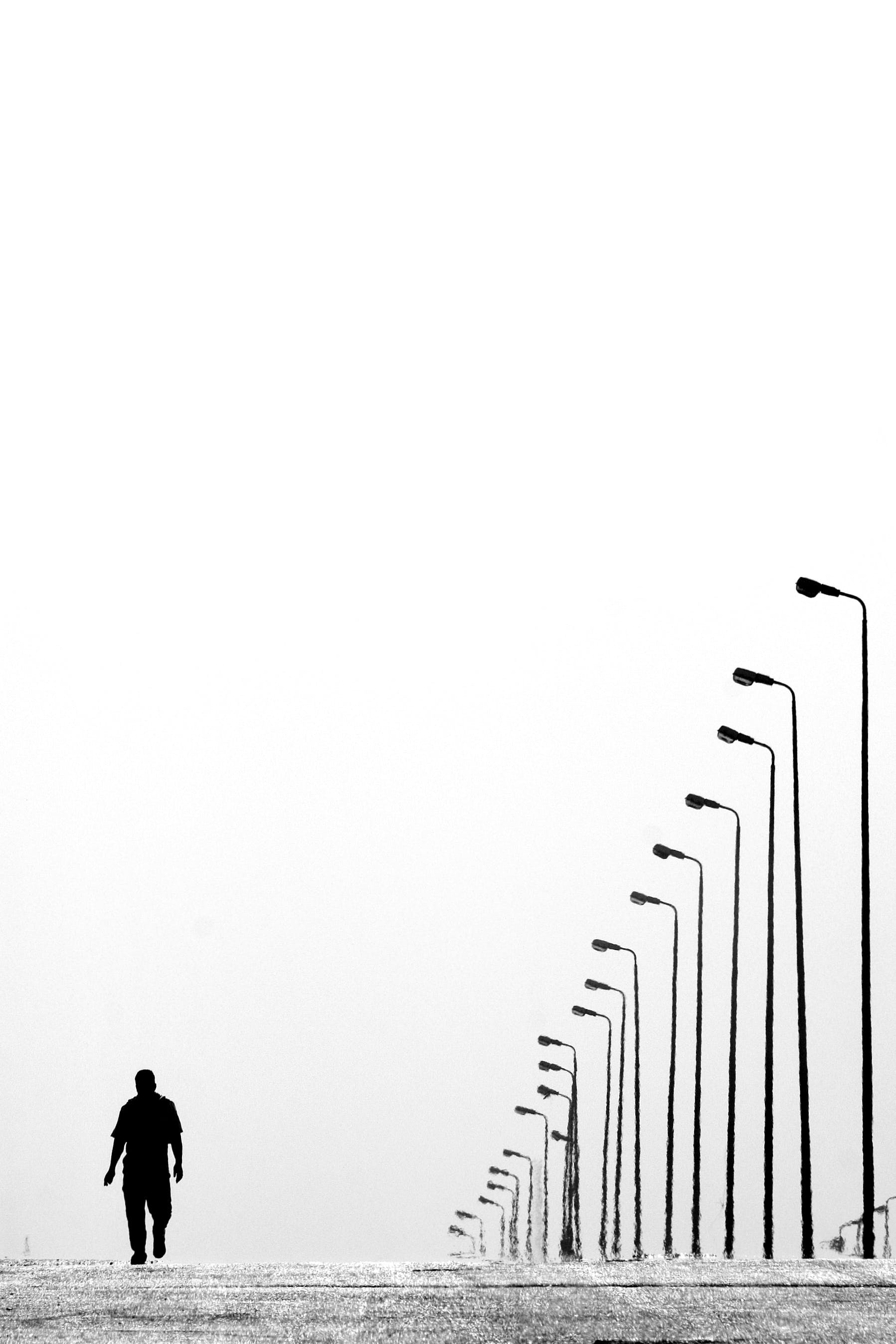 Man Walking Near Aligned Lamp Post