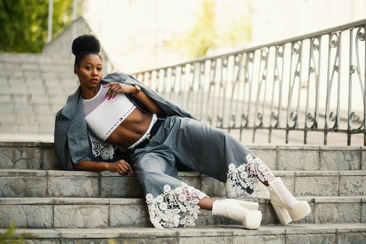 Woman Wearing White Sports Bra and Gray Pants Laying on Stairway