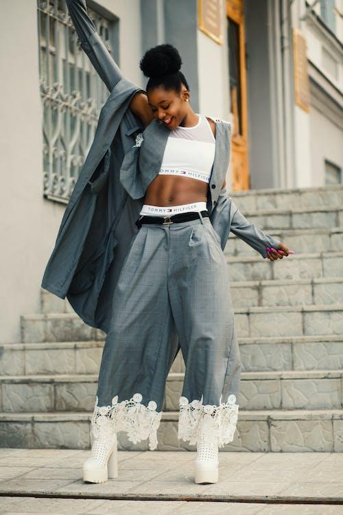Женщина в сером пиджаке стоит на сером бетонном полу
