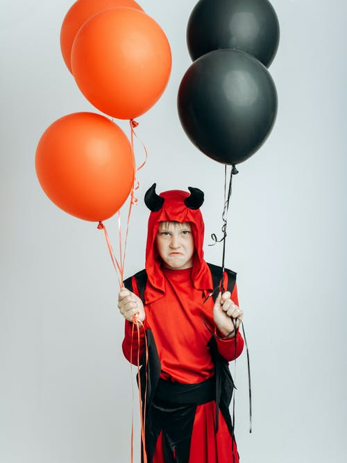 Woman in Red and Black Zip Up Jacket Holding Red Balloons