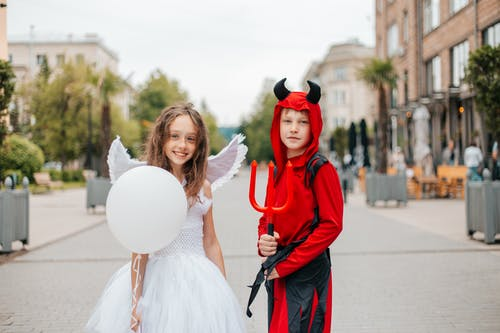 Delighted girl and boy in angel and devil costumes standing together in street on blurred background and looking at camera