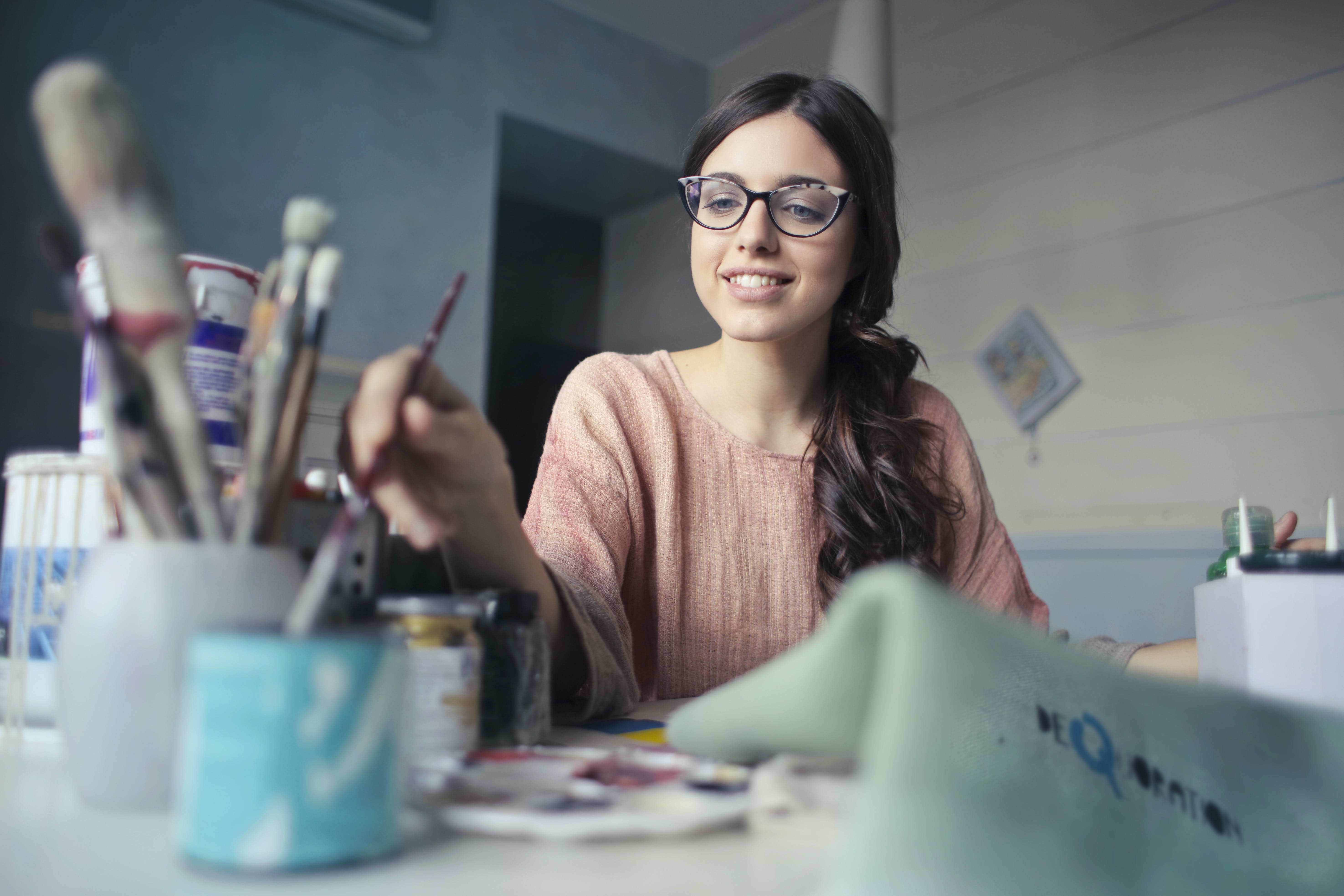 Woman in Brown Long-sleeved Shirt Wearing Eyeglasses Holding Paint Brush