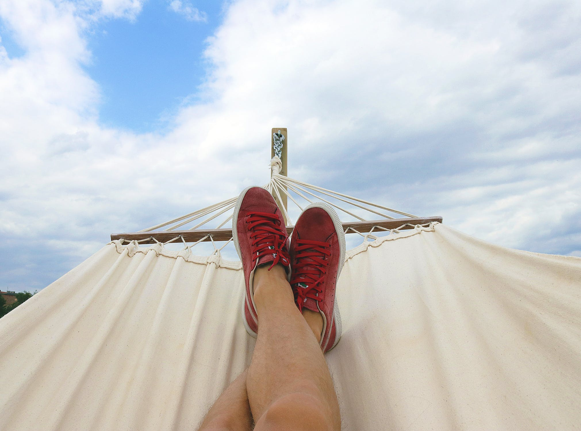 A point of view photo of someone lying in a hammock looking down at their red sneakers.