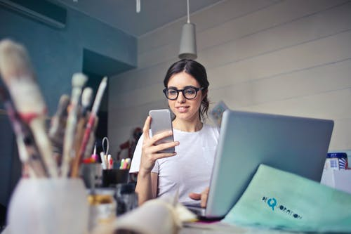 Woman in White T-shirt Holding Smartphone in Front of Laptop