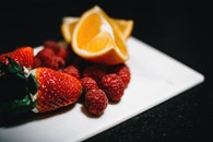 Strawberries and Sliced Wedge Oranges on White Dish