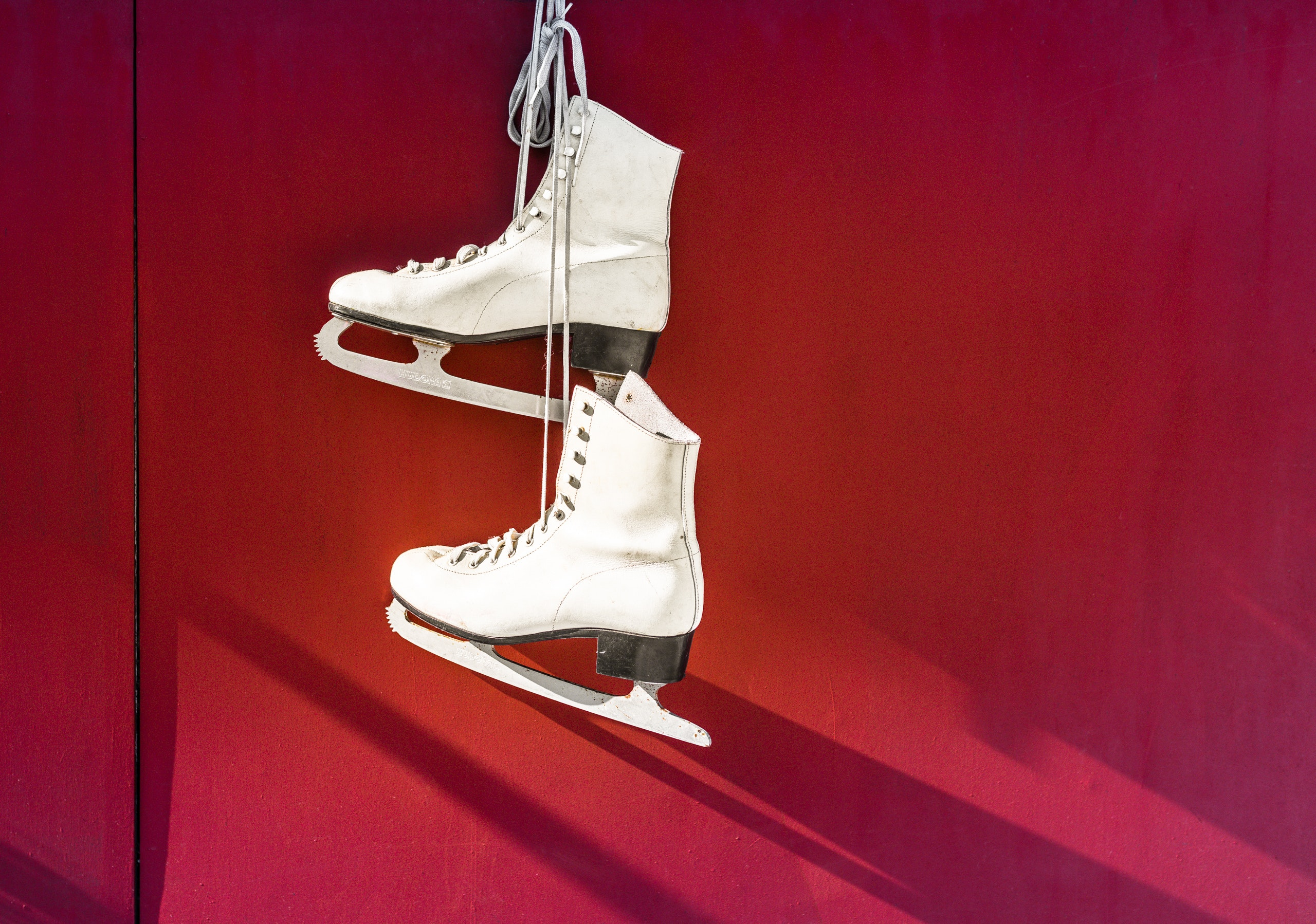 White ice skates against a red background