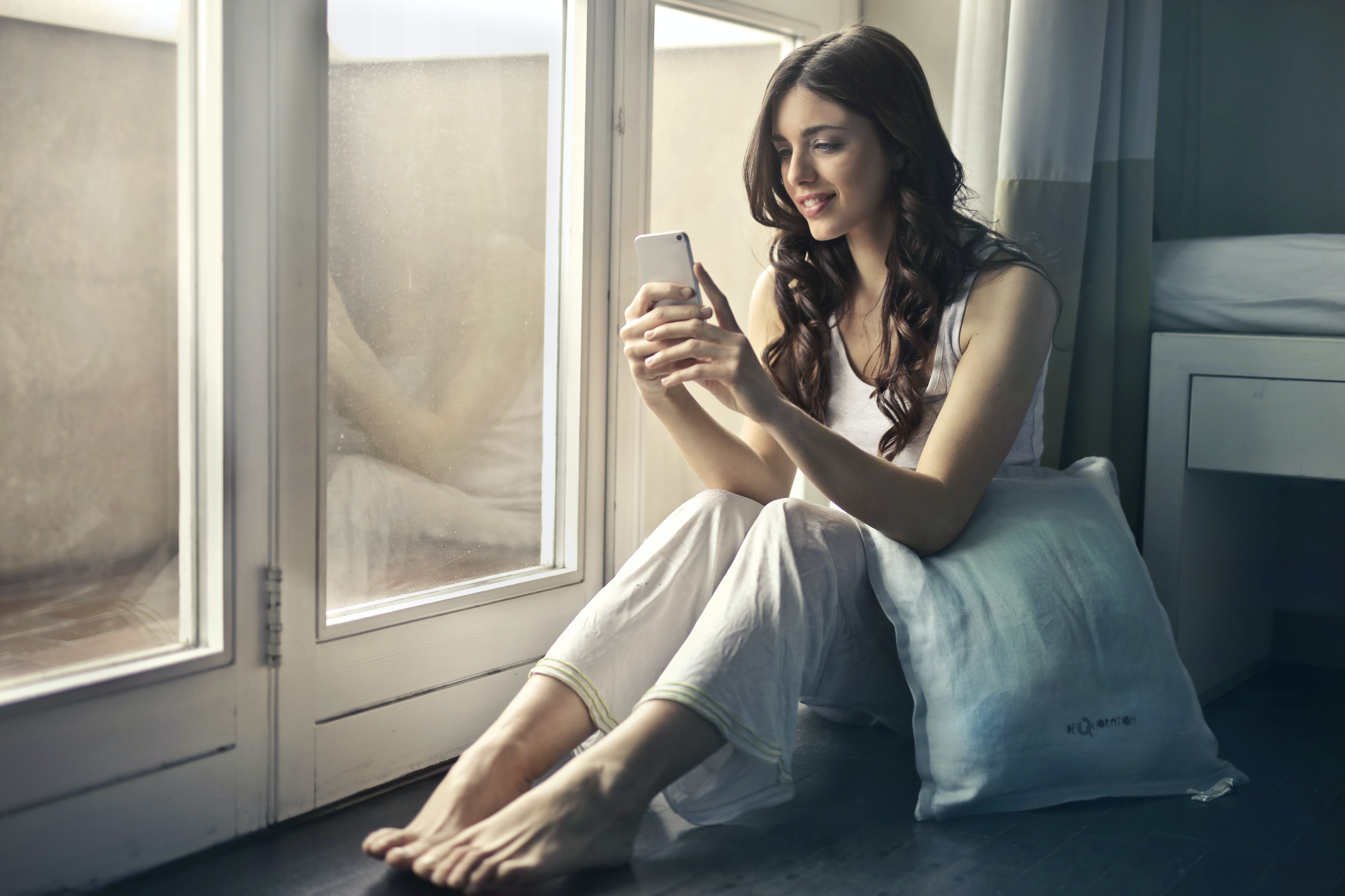 Woman Sitting Beside Window Holding Phone