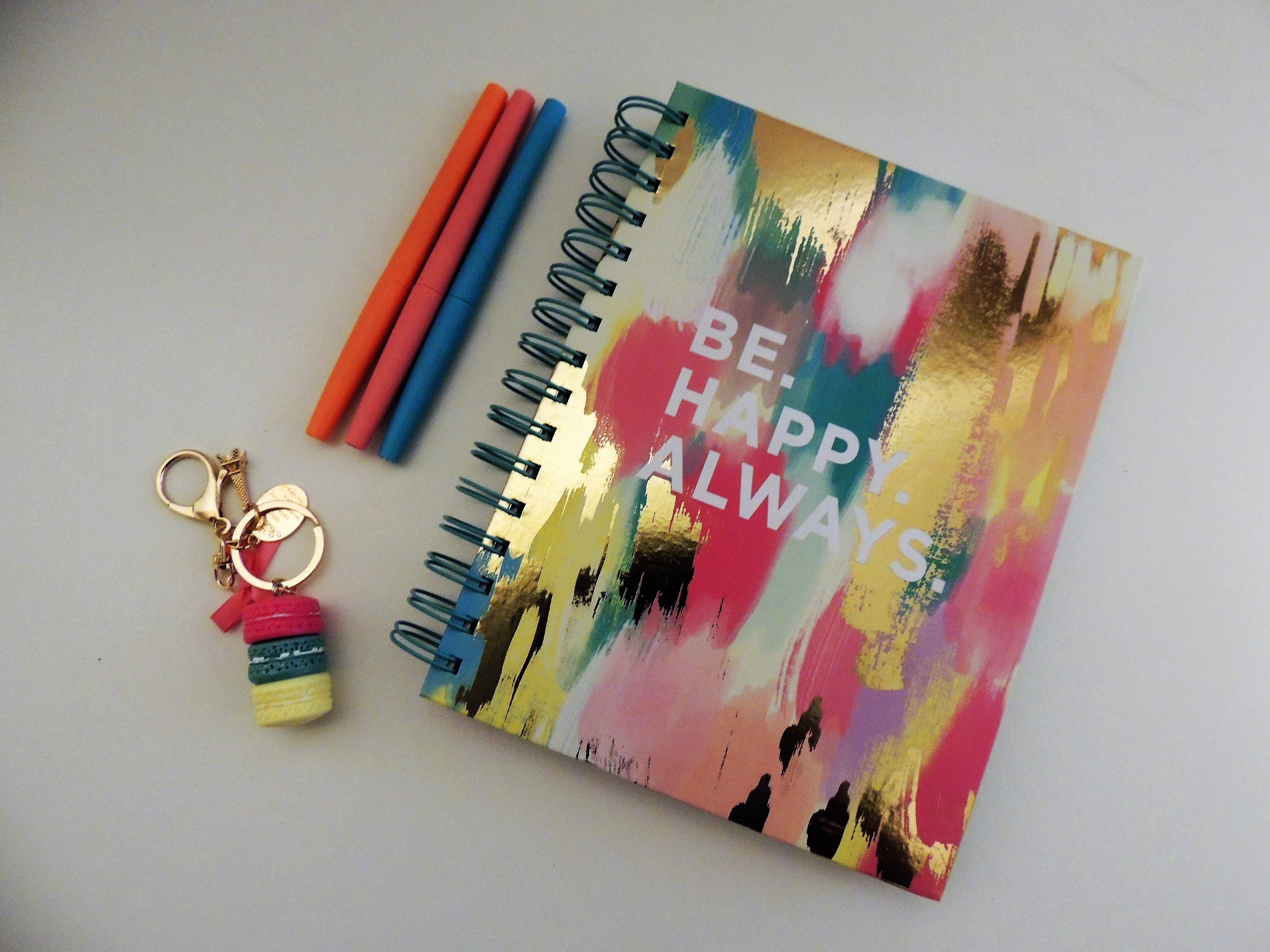 Be Happy Always Spring Notebook Beside Three Assorted-color Pens