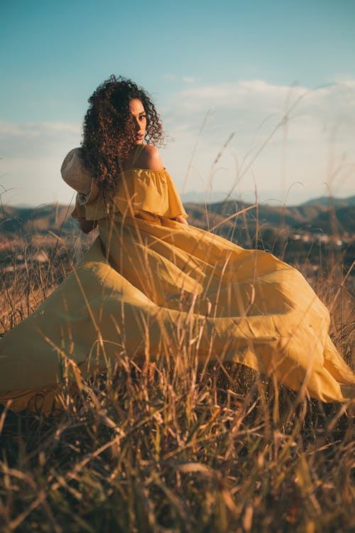 Woman in Yellow Dress Sitting on Brown Grass Field