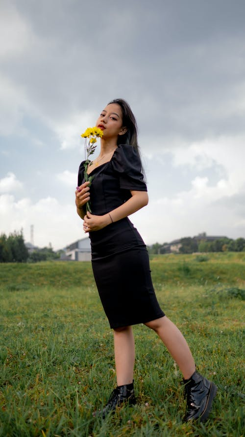 Woman in Black Dress Holding Yellow Flower