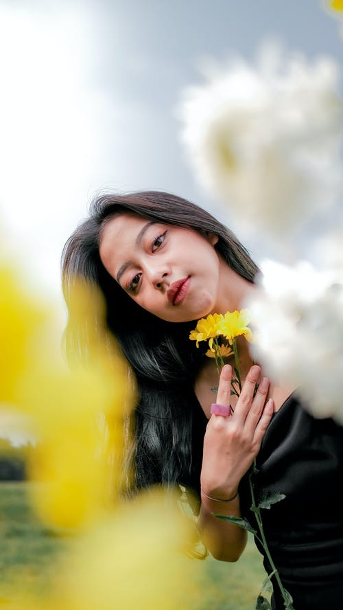 Woman in Black Jacket Holding Yellow Flower
