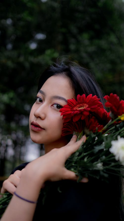 Woman in Black Shirt Holding Red and White Flowers