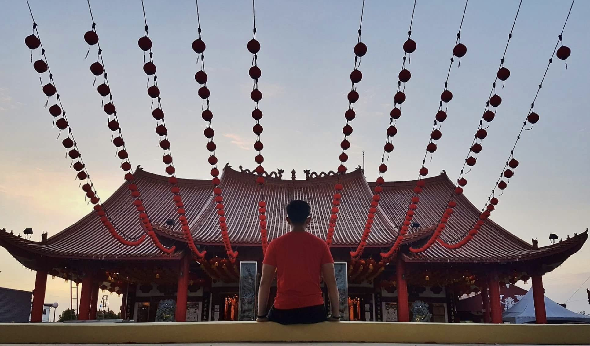 Man Sitting on Yellow Concrete Pavement Infront of Red Pagoda