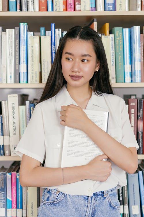 Woman Holding a Book Near a Bookshelf