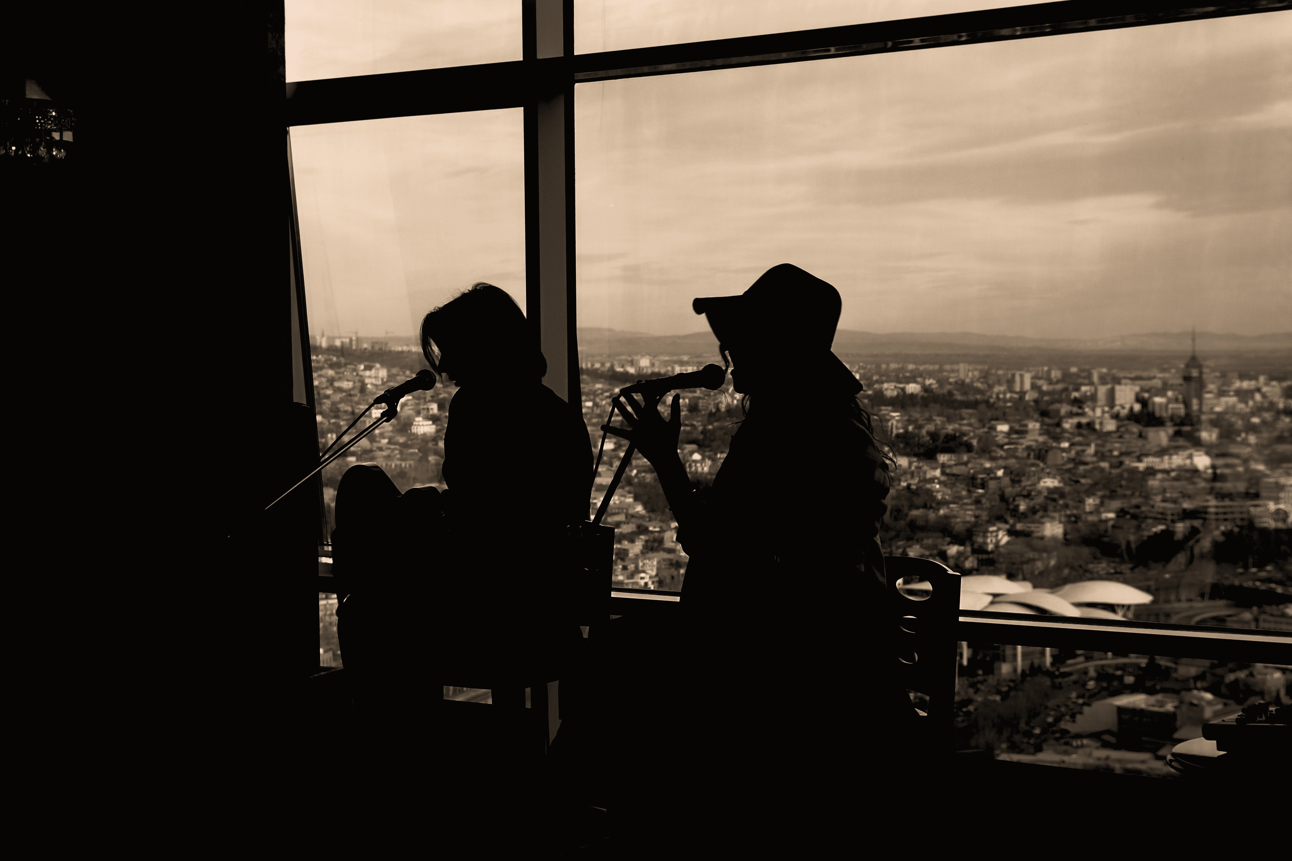 Silhouette of Two Women Singing in Sepia Photography