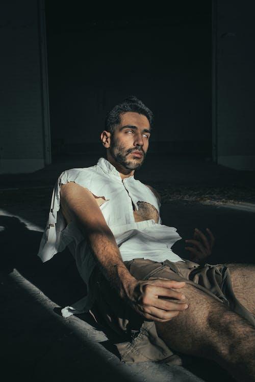 Man in White Button Up Shirt Sitting on Floor