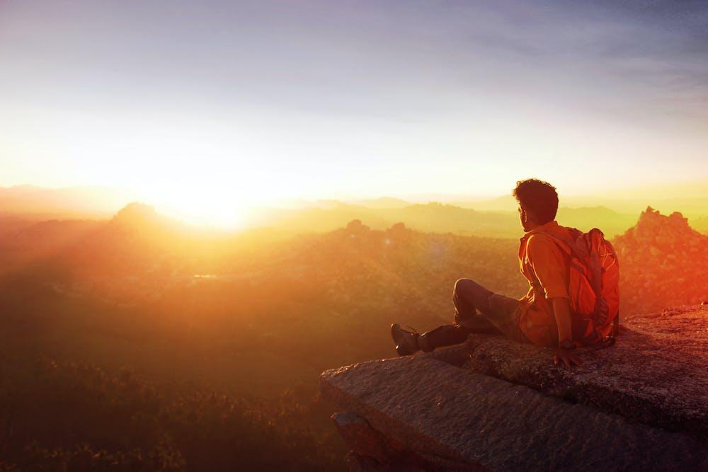 Man sitting on edge facing the sunset | Photo: Pexels