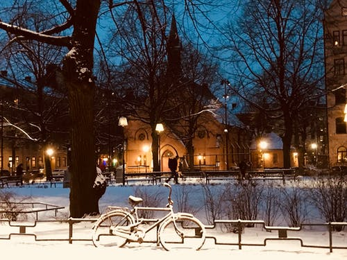 Snow Covered Bike Near Fence during Nighttime