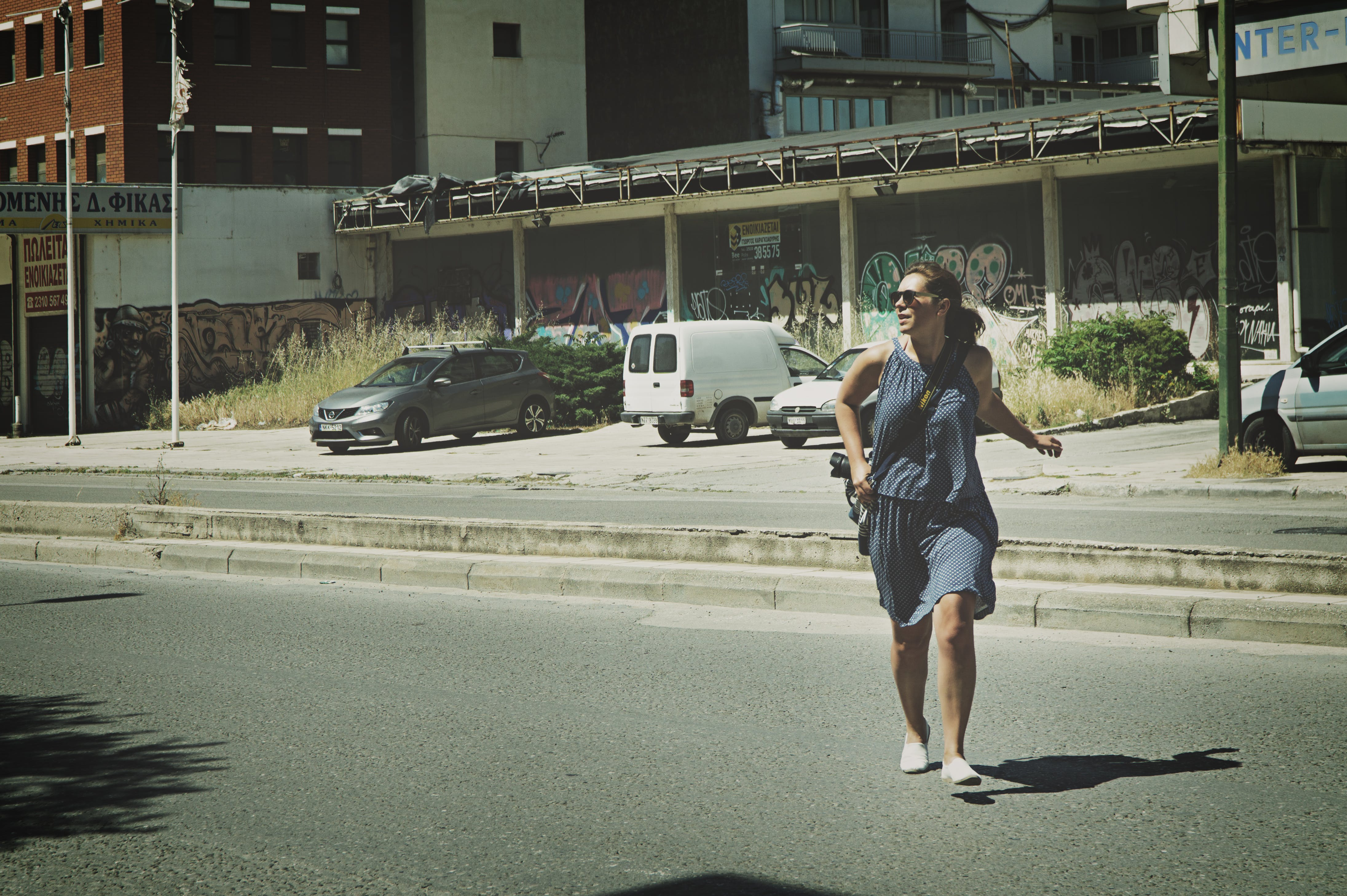 Woman Wearing Gray Tank Top Walking on Asphalt Road