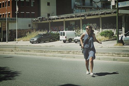 Woman Wearing Gray Tank Top Walking on Asphalt Road