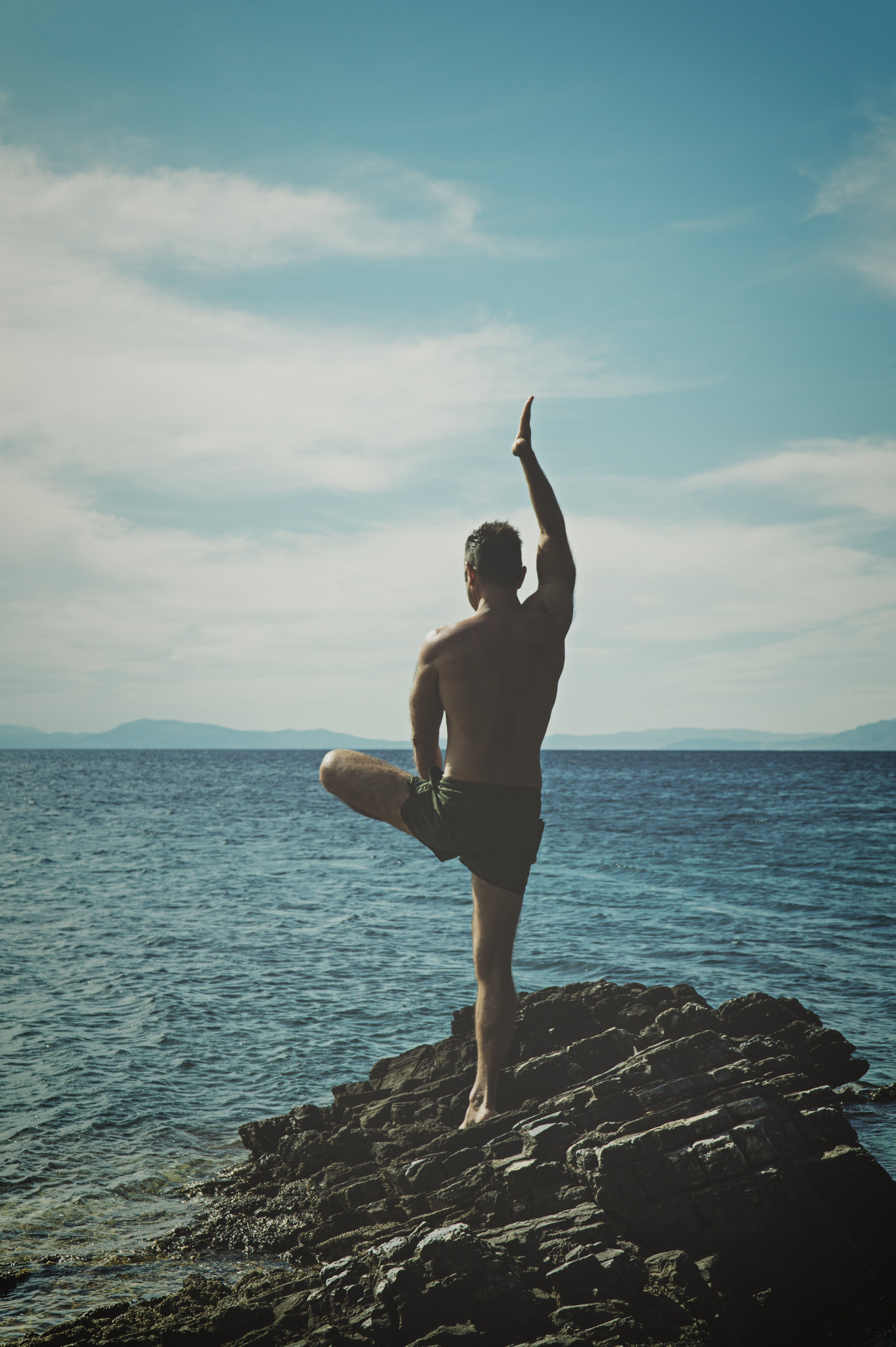 Topless Man Standing on Rock Formation Using Right Leg Only