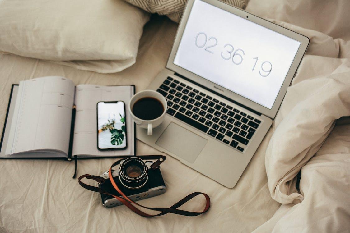 Macbook Air Beside Notebook and Camera