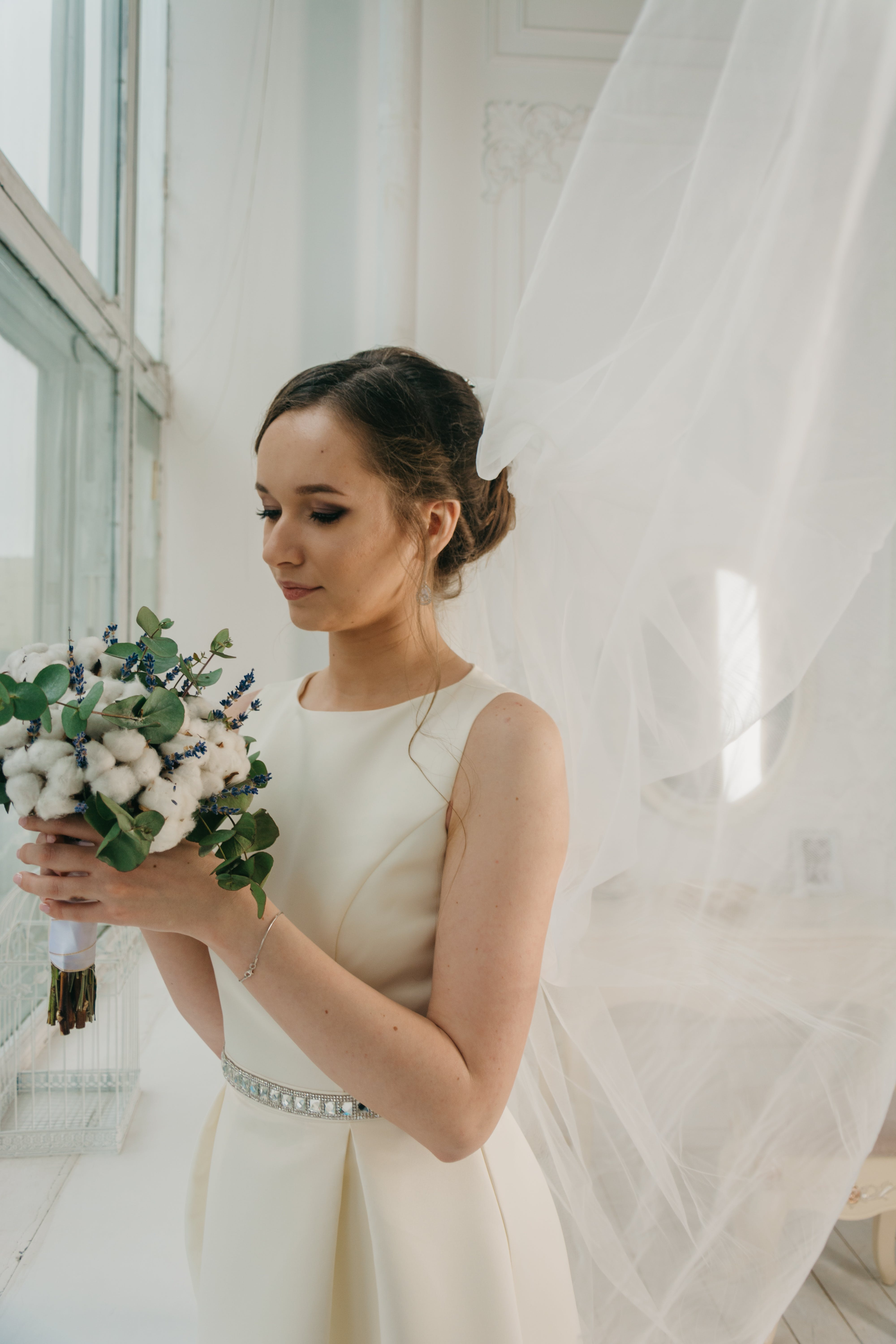 Woman in White Sleeveless Gown Holding White Flower Bouquet Infront of Window