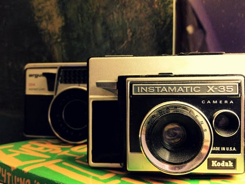 Black and Silver Camera on Green and Yellow Textile