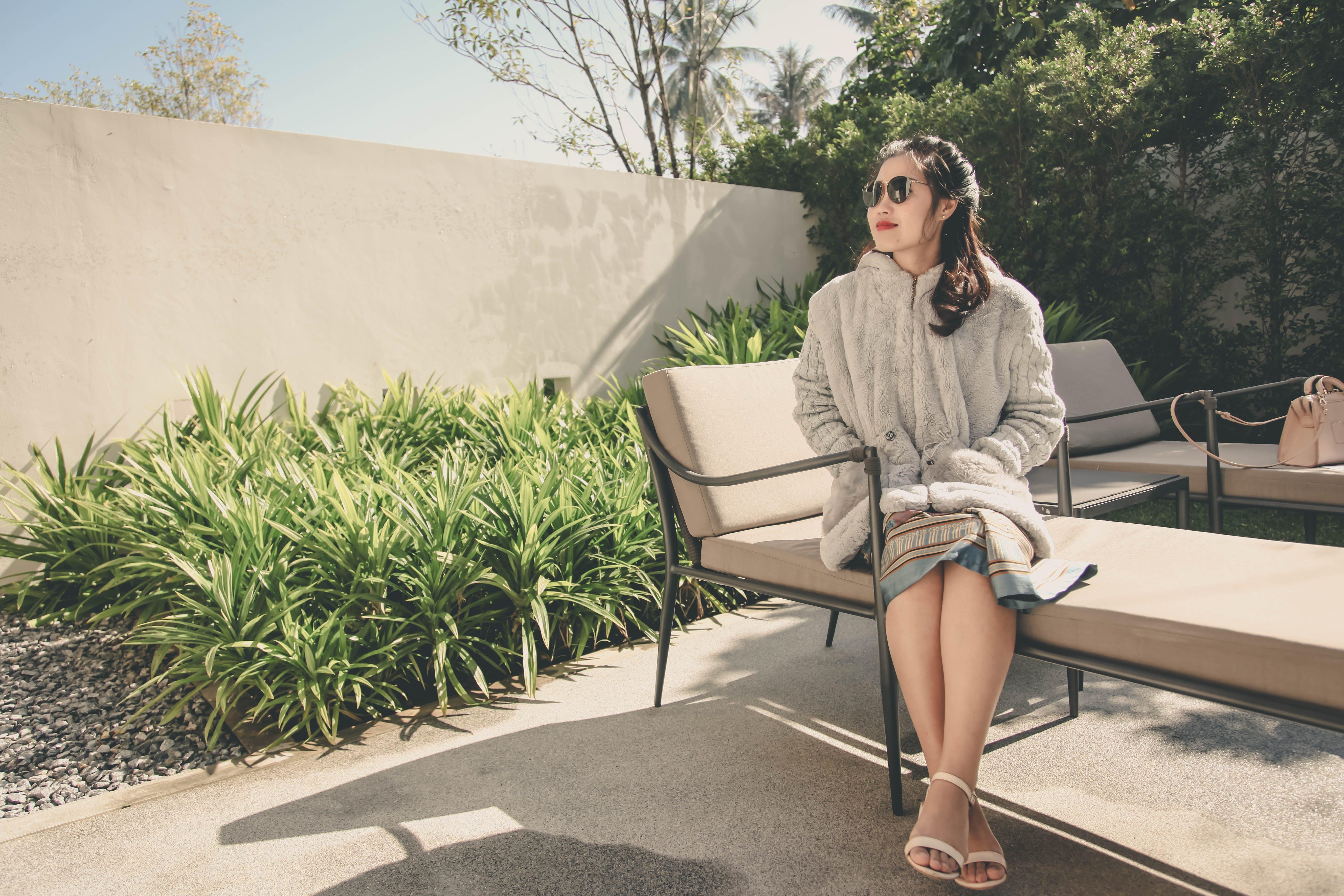 Woman Wearing Hoodie Sitting on Lounge Chair