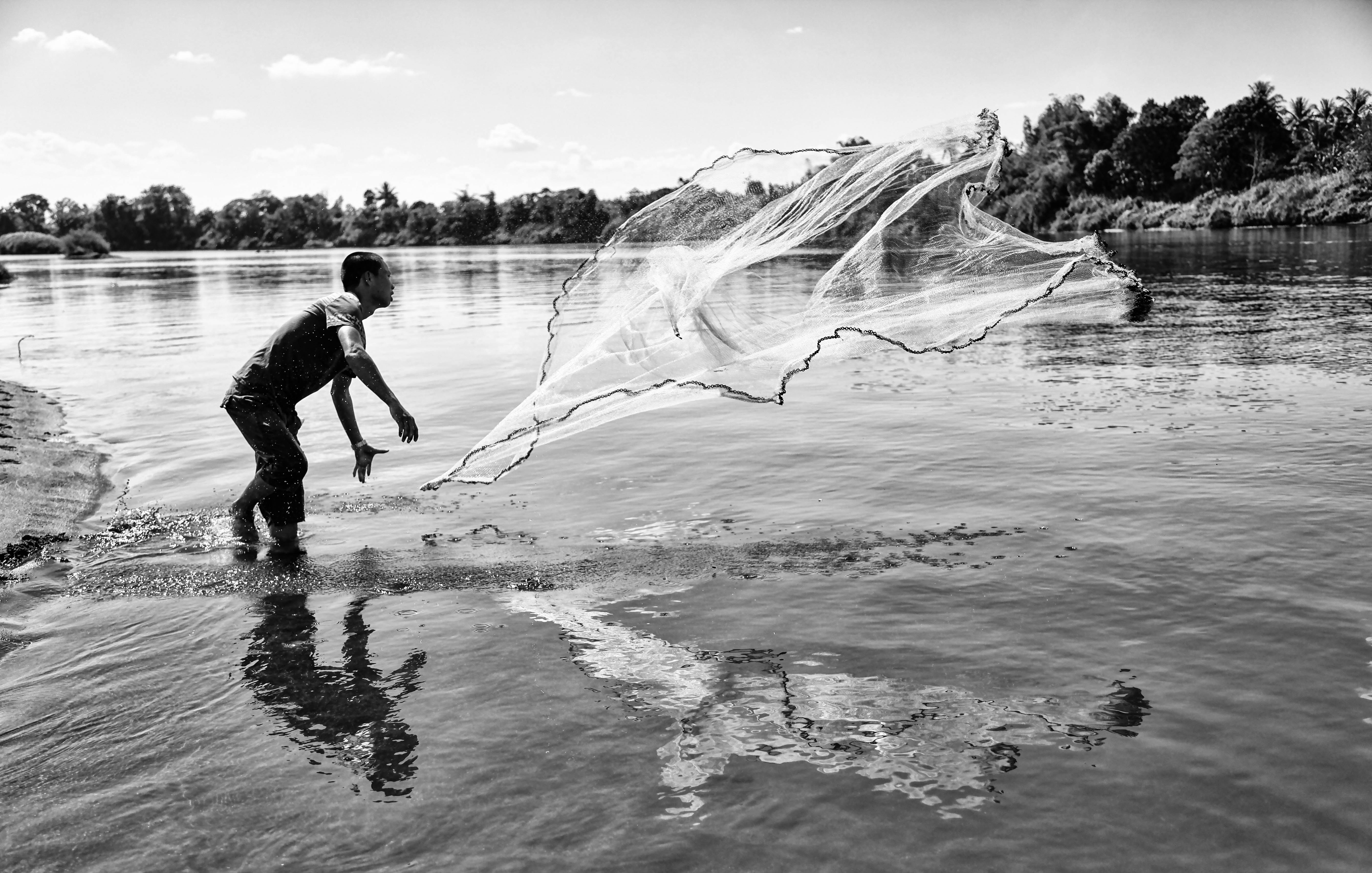 Grayscale Photo of Man Throwing a Fishing Net