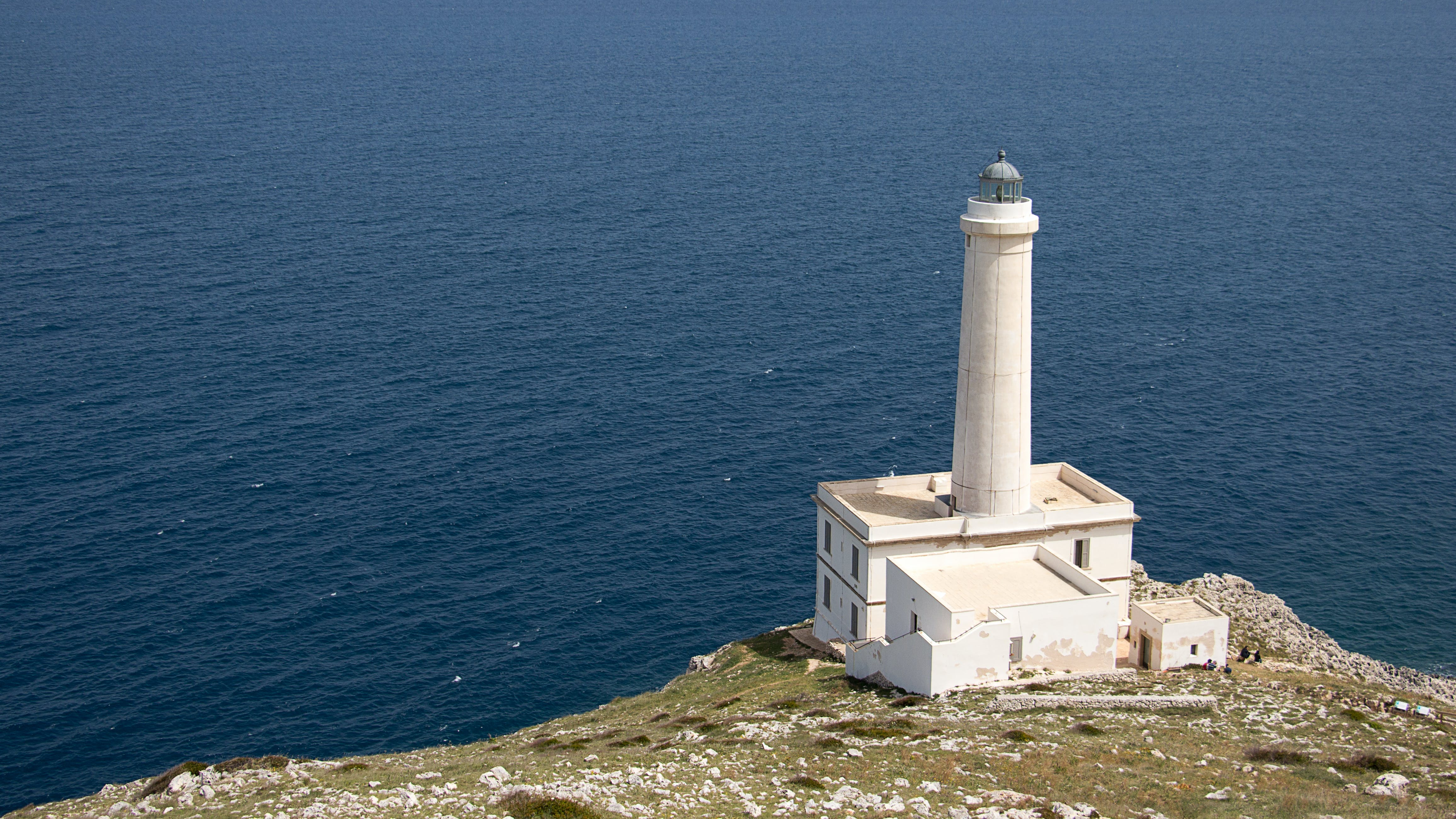 White Lighthouse on Cliff Near Body of Water
