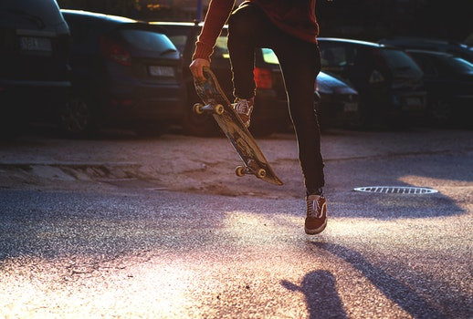 Person in Red Long Sleeved Shirt and Black Skinny Pants Riding a Skateboard