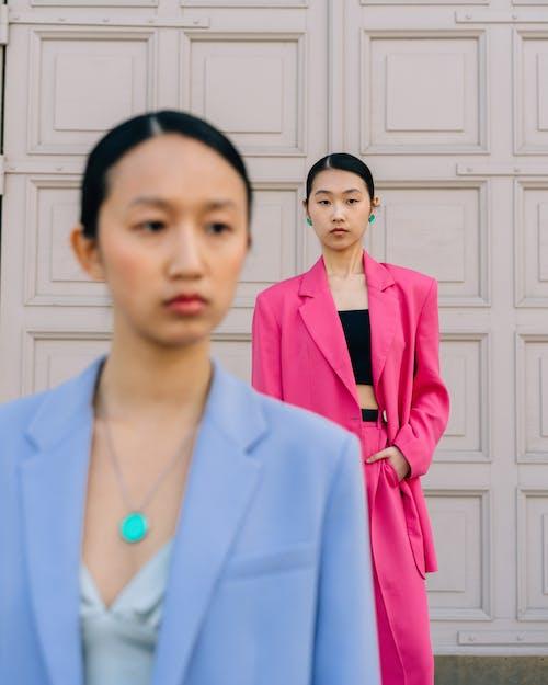Woman in Pink Blazer Standing Beside Woman in Blue Blazer