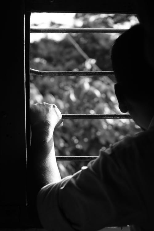 Grayscale Photo of Person Holding Window Grill