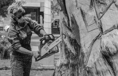 Grayscale Photo of a Person Trimming a Tree Log